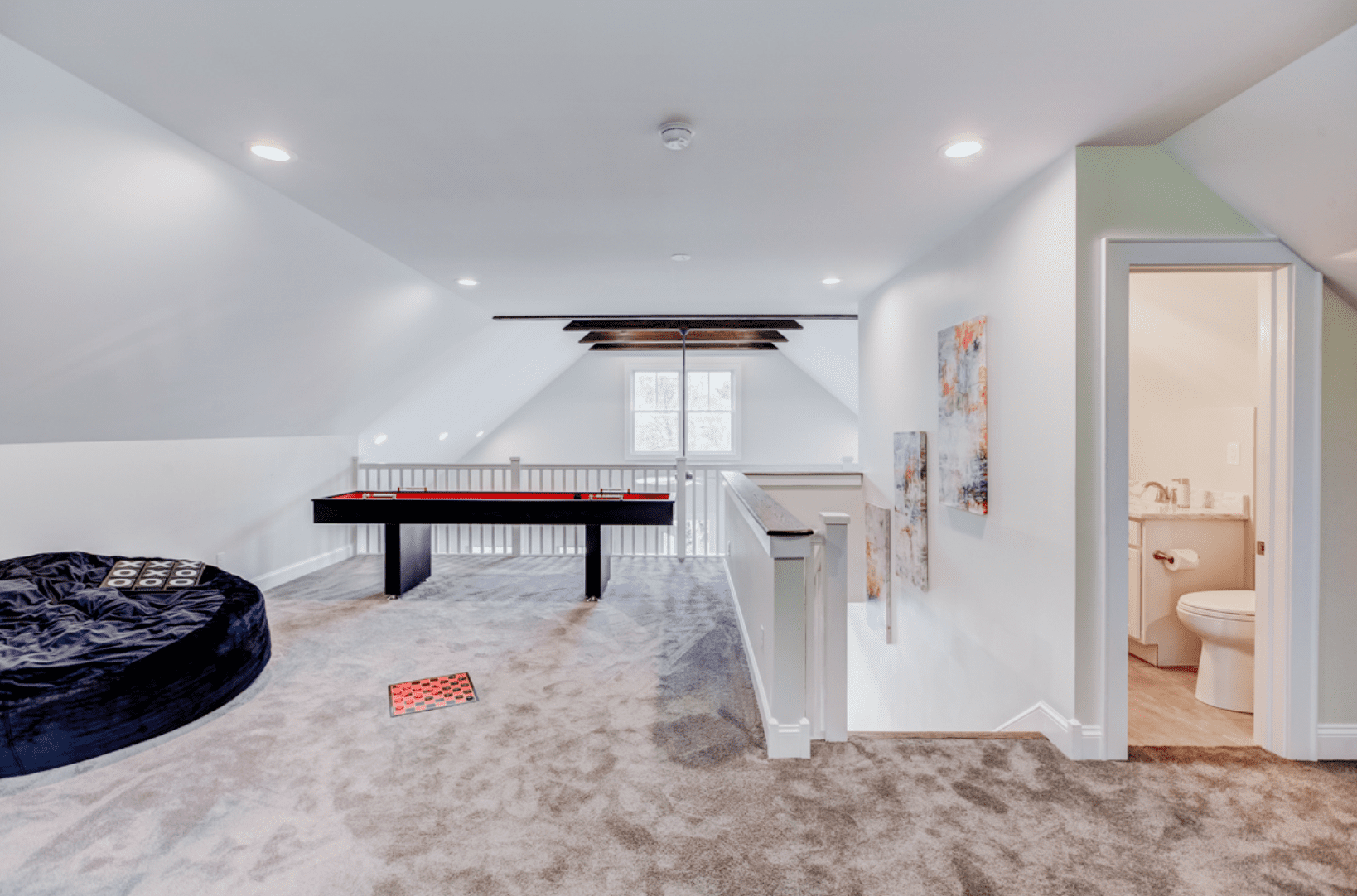 upper level game room with pool table, bathroom, and bean bag chair