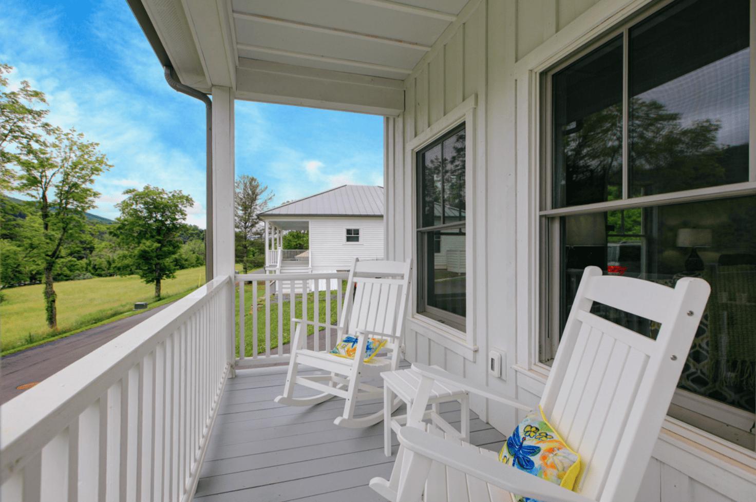 white rocking chairs sitting on white porch